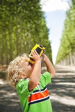 Boy (2-3) looking through binoculars