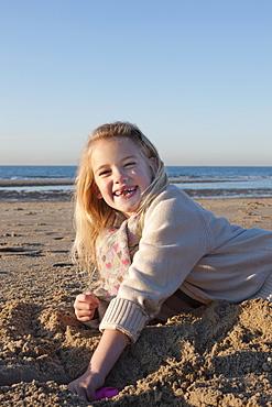 Netherlands, Zeeland, Haamstede, Girl digging sand on beach, Netherlands, Zeeland, Haamstede