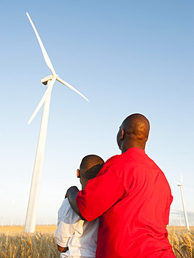 USA, Oregon, Wasco, Father and son (8-9) standing in wheat field, watching wind turbine