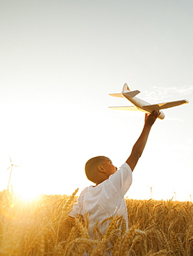 Boy (10-11) playing with toy aeroplane in wheat field