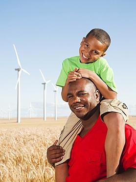 USA, Oregon, Wasco, Boy (8-9) piggy-back riding on father, wind turbines in background