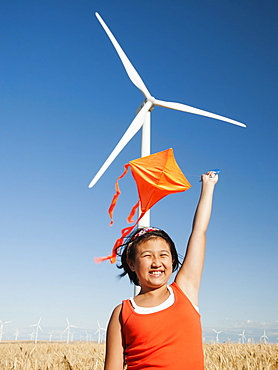 USA, Oregon, Wasco, Girls 10-11) playing with kite in wheat field, wind turbine in background