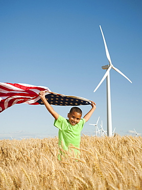 USA, Oregon, Wasco, Boy (8-9) flying american flag in wheat field with wind turbines in background