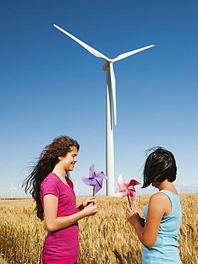 USA, Oregon, Wasco, Girl (10-11, 12-13) holding fans in wheat field in front of wind turbines