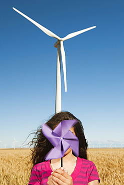 USA, Oregon, Wasco, Girl (12-13) holding fan n front of wind turbines