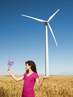 USA, Oregon, Wasco, Girl (12-13) holding fan in wheat field in front of wind turbines