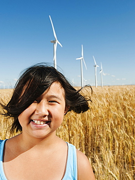 USA, Oregon, Wasco, Cheerful girl (10-11) standing in wheat field with wind turbines in background
