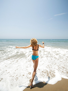 Happy young woman running in to sea