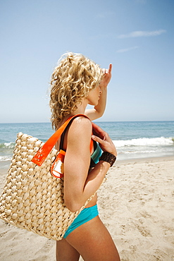 Young attractive woman carrying straw bag on sandy beach