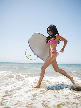 Young attractive woman running into water with swimming boards