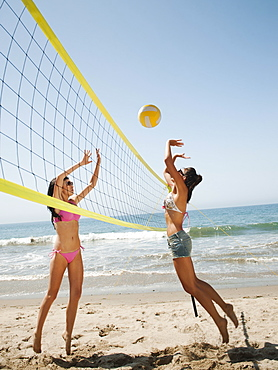 Two attractive young women playing beach volleyball