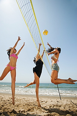 Three attractive young women playing beach volleyball