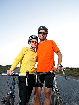 Couple of cyclists posing for portrait on empty road