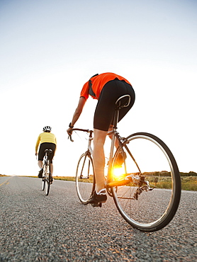 Mid adult couple cycling on empty road