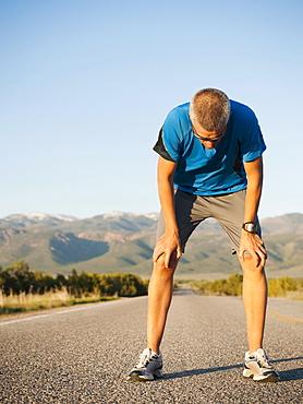 Mid adult man taking break from running on empty road