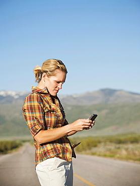 USA, Utah, Kanosh, Mid adult woman calling emergency services on empty desert road