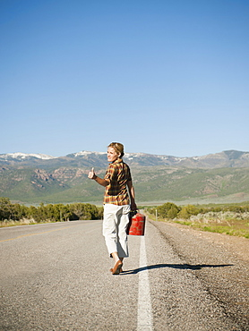 Mid adult woman carrying empty canister attempting to stop vehicles for help
