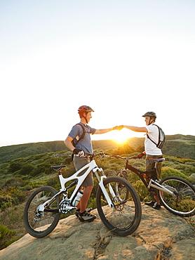 USA, California, Laguna Beach, Two bikers on hill doing fist bump