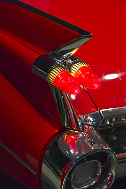 Tail fin on a 1959 red automobile