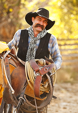 Cowboy holding saddle