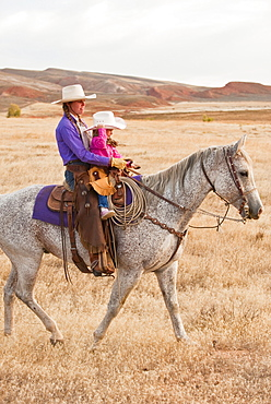 Mother and daughter riding horse