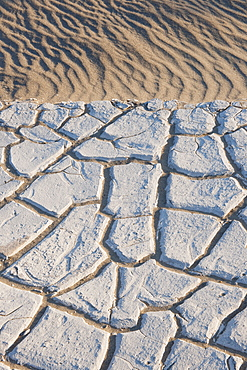 Sand dunes in the desert with cracked earth