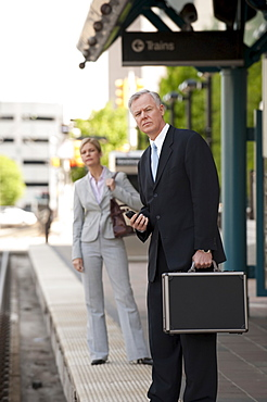 Two business people at a train station