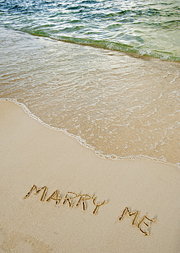 Marry me message written in sand