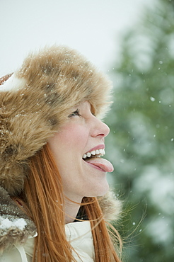 Woman catching snow on tongue