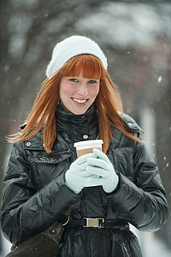 Woman holding coffee in snow