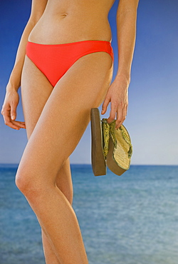 Midsection of woman in bikini holding flip-flops on beach