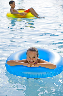 Children playing with inflatable tubes in swimming pool