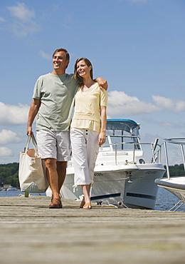 Couple walking on boat dock