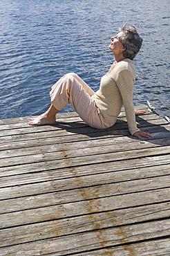 Senior woman sitting on dock