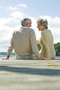 Senior couple sitting on dock