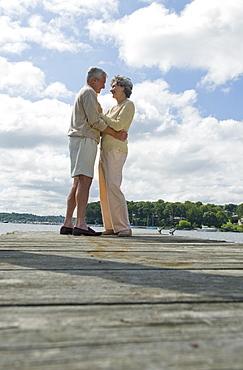 Senior couple hugging on dock