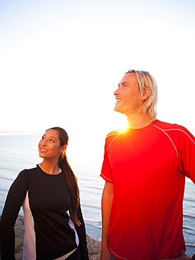 Portrait of male and female joggers at sea