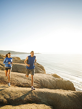 USA, California, San Diego, Man and woman jogging along sea coast