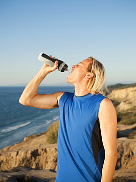 USA, California, San Diego, Male jogger drinking water from bottle