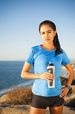 USA, California, San Diego, Portrait of female jogger holding water bottle