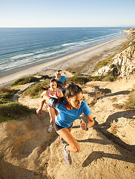 USA, California, San Diego, Three people jogging along sea coast
