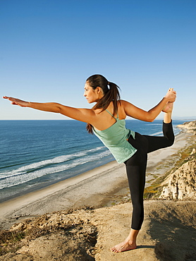 USA, California, San Diego, Woman practicing yoga on beach