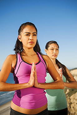 USA, California, San Diego, Two women practicing yoga on beach