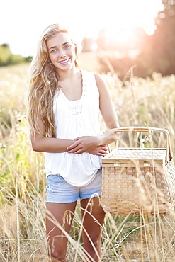 Outdoors portrait of teenage (16-17) with picnic basket