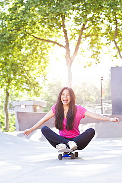 Cheerful young woman sitting on skateboard