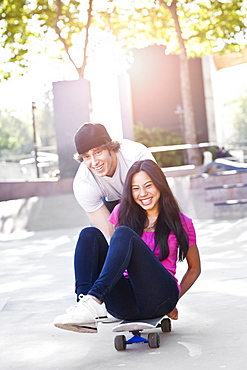 Young multi-racial couple playing with skateboard