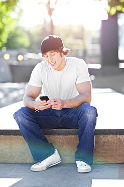 Young man sitting outdoors, text messaging