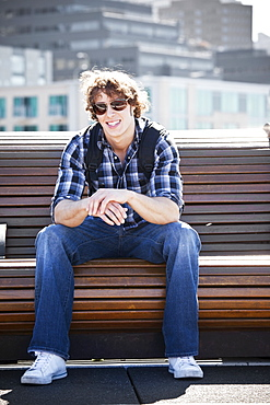 USA, Washington, Seattle, Young man sitting on bench