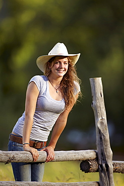 Portrait of cowgirl leaning on fence