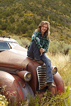 USA, Colorado, Portrait of woman resting on abandoned truck in desert